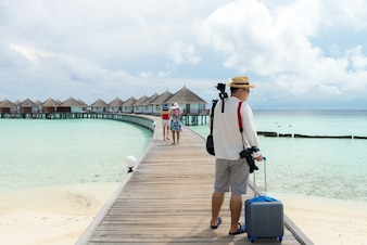 Asian traveler stand on wooden bridge with luggage camera tripod looking to the beautiful