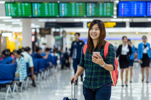 Asian traveler with luggage holding the smart mobile phone for check-in over the flight board