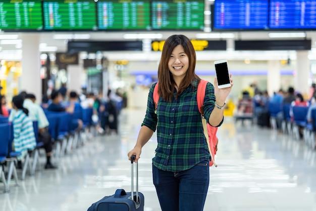 チェックインのためのスマート携帯電話を示す荷物を持つアジアの旅行者