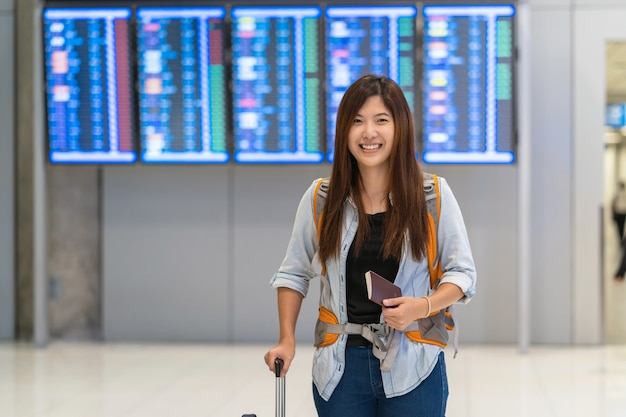 Asian traveler with luggage with passport walking over the flight board for check-in