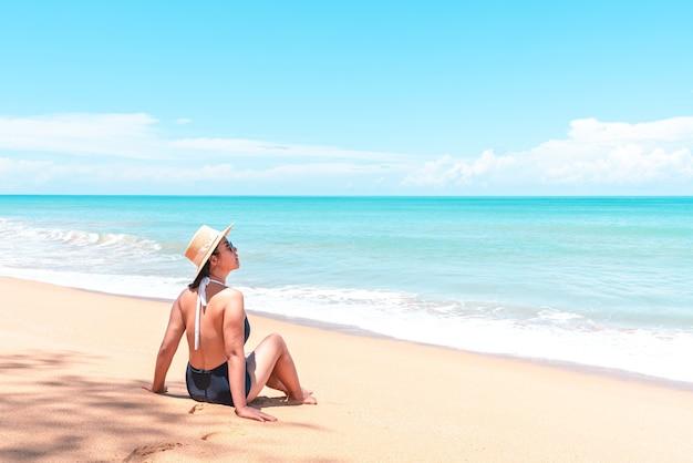 水着と麦わら帽子をかぶったアジア人旅行者の女性がビーチに座って眺めを見る