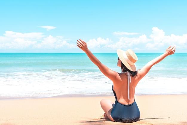 アジアの旅行者の女性は、リラックスしてビーチに座って眺めを眺めるために両腕を上げます
