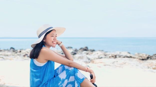 Азиатская женщина путешественника сидит и расслабляется на пляже на фоне моря. концепция счастливого путешествия на выходных в отпуске.