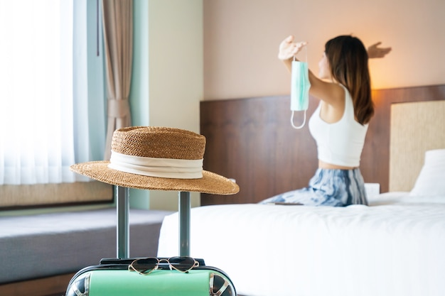 アジアの旅行者の女性は、サージカルフェイスマスクを脱いでホテルの部屋のベッドでリラックスします。旅行とヘルスケアの概念