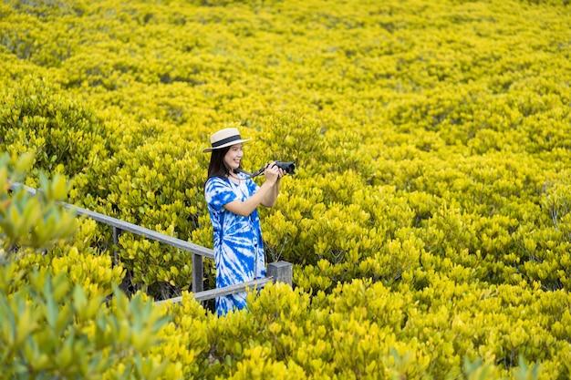 Азиатская женщина-путешественница, делающая фото камерой на деревянном мосту для путешествий