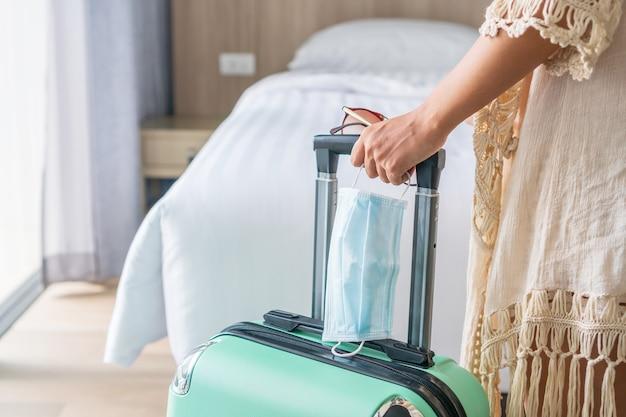 チェックイン後、ホテルの部屋で緑の荷物とサージカルマスクを持つアジアの旅行者の女性。旅行、ヘルスケア、新しい通常のコンセプト。