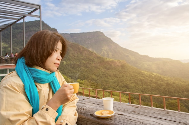 Asian traveler woman with scarf drinking a cup of espresso coffee and enjoy nature view of the mountain landscape in the morning with sunlight