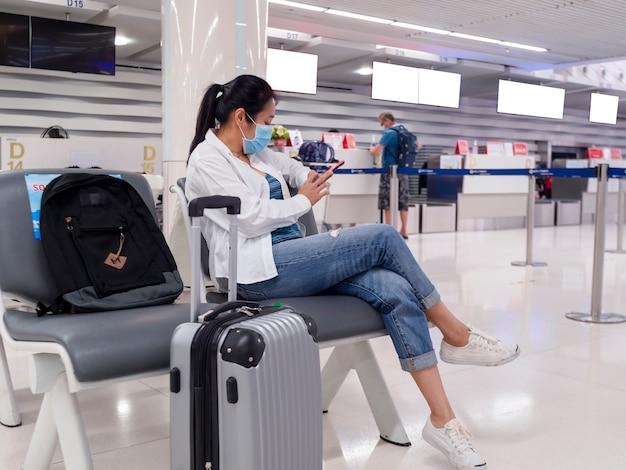 アジアの旅行者の女性は、コロナウイルスから社会的な距離の椅子に座っているフェイスマスクを着用します