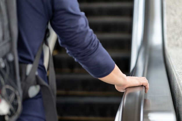 Asian traveller's man holding hand rail go up stairs