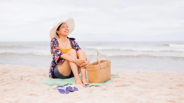 アジアの旅行者の女性は週末の休暇で海沿いのビーチに座ってリラックス