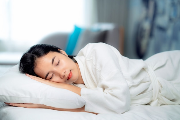 Азиатский путешественник женщина спит и расслабится в постели отеля