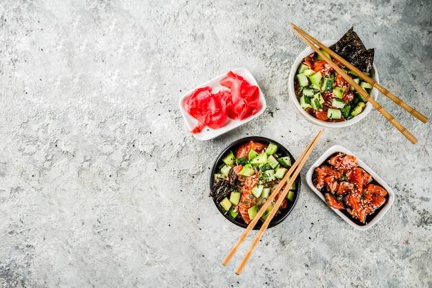 Asian trendy food sushi poke bowl with cucumber salmon avocado black and white sesame seeds
