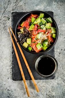 Asian trendy food, sushi poke bowl with cucumber, salmon, avocado, sesame seeds
