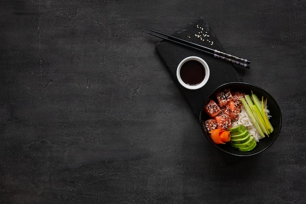 Asian trendy food, sushi poke bowl with cucumber, salmon, carrot, avocado, sesame seeds