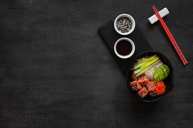 Asian trendy food, sushi poke bowl with cucumber, salmon, carrot, avocado, sesame seeds