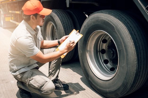 Asian truck driver holding clipboard inspecting safety check a truck tire