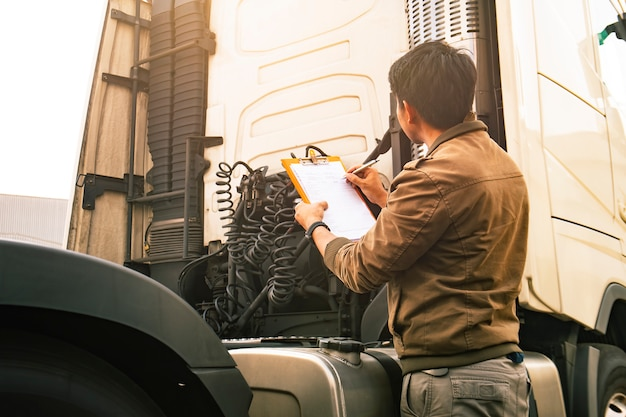 Asian truck driver holding clipboard inspecting safety vehicle maintenance checklist of modern semi truck.