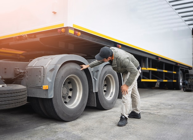 Asian a truck driver is checking trailer truck wheels and tires inspection maintenance and safety