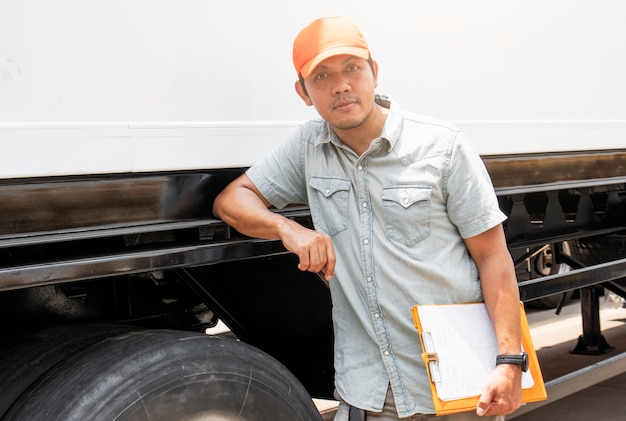 Asian a truck driver standing with trailer truck truck inspection and safety driving