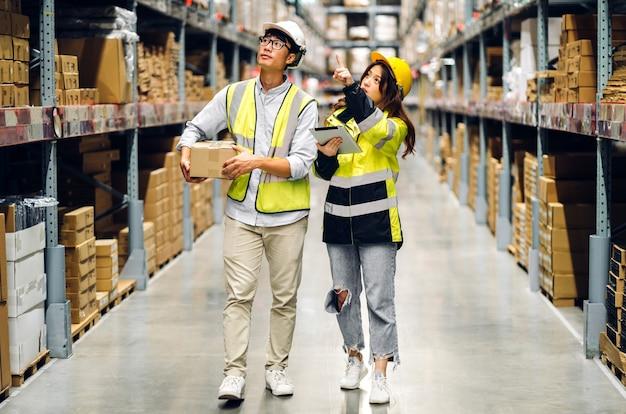 헬멧 팀의 아시아 2명의 엔지니어는 창고에서 상품을 확인하기 위해 태블릿 컴퓨터에서 세부 사항을 주문합니다. 프리미엄 사진