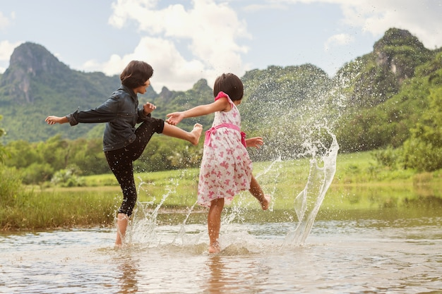 Asian two girls happy playing in the river. children having fun outdoors on summer lifestyle