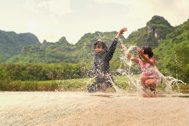 Asian two girls happy playing in the river. children having fun outdoors