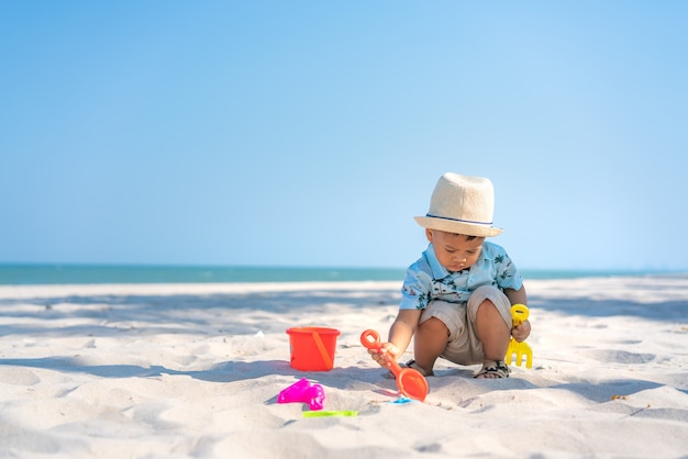 Asian two year old toddler boy playing with beach toys on beach.
