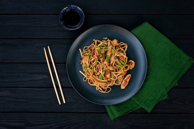 Asian udon noodles with chicken vegetables and teriyaki sauce on a black wooden background