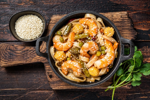 Asian udon stir-fry noodles with shrimps prawns in a pan. dark wooden background. top view.