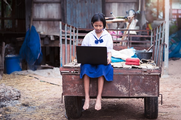 Asian uniform student girl using computer notebook in countryside of thailand
