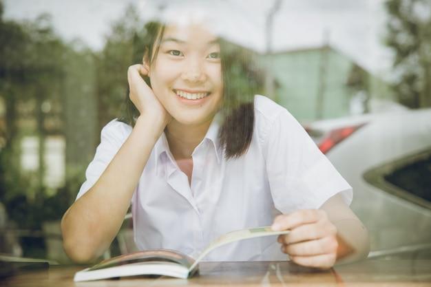ガラス窓の影を通して見ているアジアの大学の女の子の十代のかわいい笑顔は、本を読んで座っている間効果を反映します
