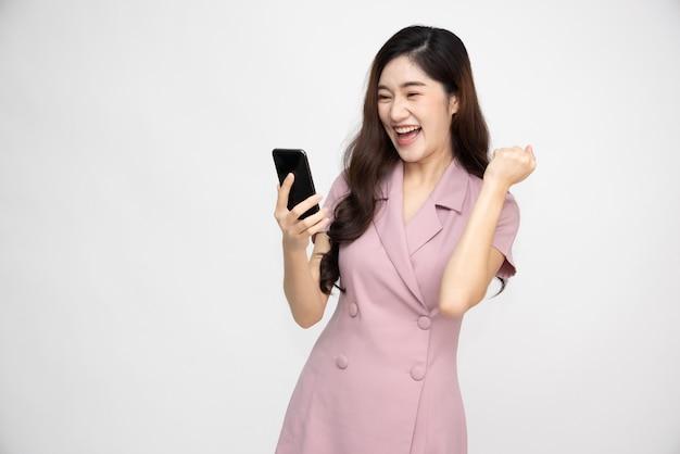 스마트폰을 사용하고 흰색 배경 위에 흥미진진한 아시아인
