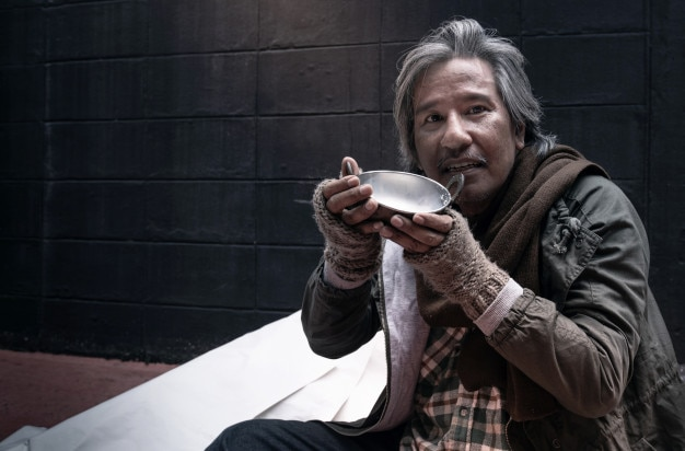 Asian vagrant feel happy with the donated milk, homeless and hungry vagrant holding a cup of milk