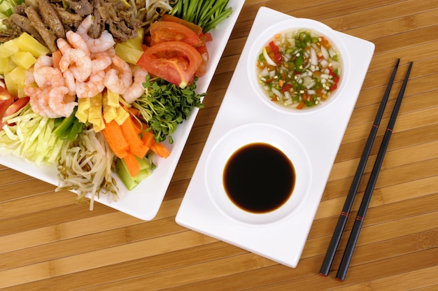 Asian vegetables with soy sauce and chopsticks
