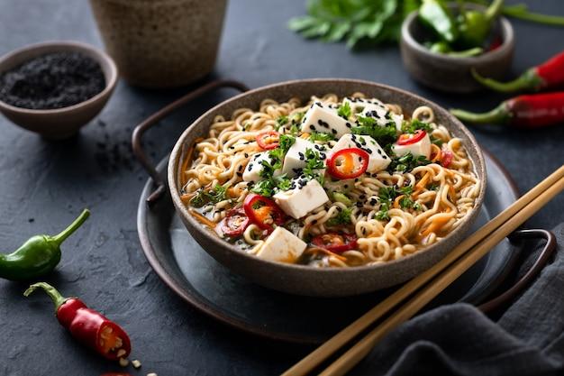 아시아 채식 음식, 어두운 표면에 두부와 야채, 선택적 초점라면