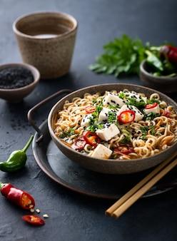 暗い表面の選択的な焦点に豆腐と野菜を使ったアジアのベジタリアンフードラーメン