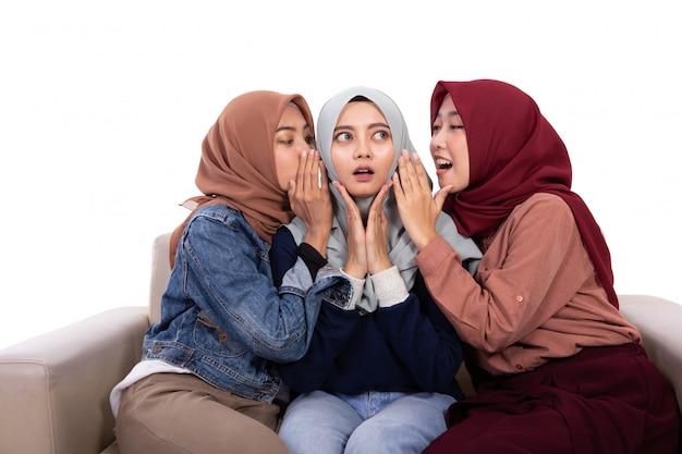 Asian veiled women surprised when her friend whispered