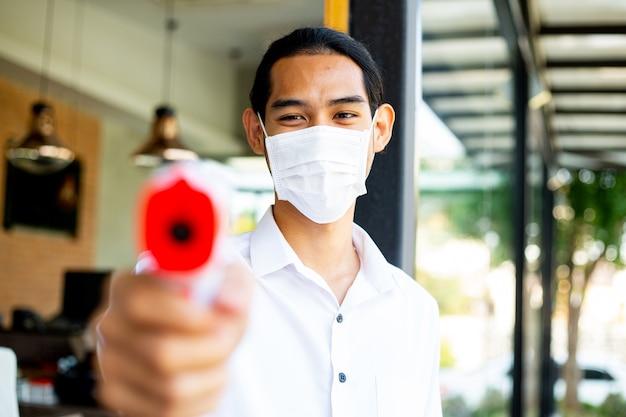 식당에 들어가기 전에 고객 발열 증상을 확인하기 위해 온도계 총을 들고 있는 아시아 웨이터. covid-19 건강한 환자를 예방하고 선별합니다.