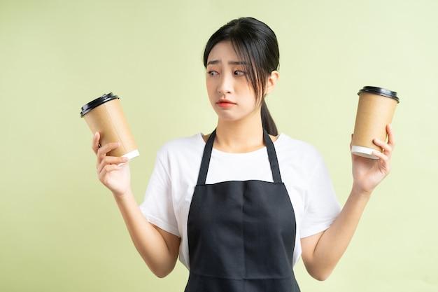 커피 두 잔을 들고 아시아 웨이트리스