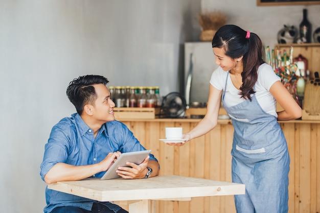 コーヒーを提供するアジアのウェイトレス