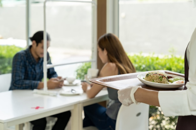 アジアのウェイトレスが新しい通常の料理を出します。