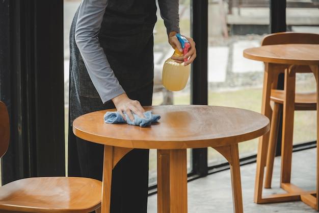 카페 커피 숍 레스토랑 호텔에서 감염 코로나 바이러스 (covid-19)를 보호하기 위해 소독제 스프레이가있는 앞치마 청소 테이블에 아시아 웨이트리스 직원 서비스 여성. 새로운 일반 개념