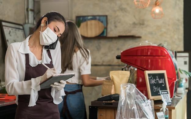Азиатская официантка принимает заказ с мобильного телефона для заказов на вынос и самовывоз.