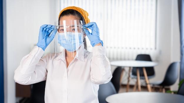 Азиатская официантка носит маску для лица и защитную маску для защиты от вспышки вируса