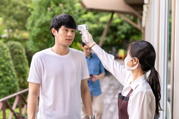 Asian waitress with face mask taking temperature to customer before getting in restaurant with social distance queue in line. new normal restaurant concept after coronavirus covid-19 pandemic.