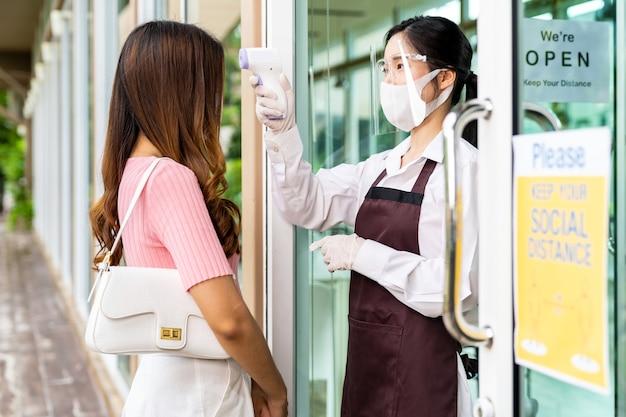 レストランに入る前に女性客の女性に温度を取る顔のマスクを持つアジアのウェイトレス。コロナウイルスcovid-19パンデミック後の新しい通常のレストランのコンセプト。