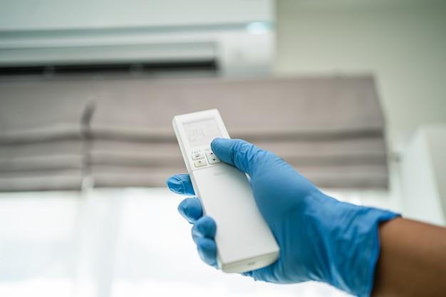 Covid19コロナウイルスを保護するために壁のリモコンのエアコンを押すためのアジアの着用手袋