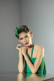 빨간 립스틱과 녹색 드레스를 입은 아시아 백인 소녀가 의자에 앉아 있습니다.
