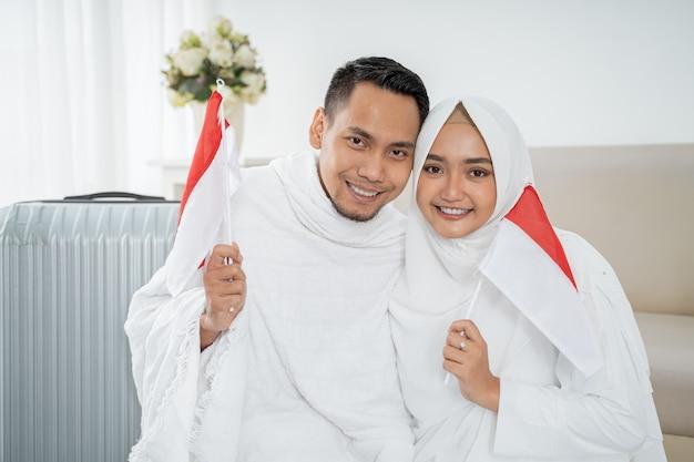 アジアの妻と夫のインドネシアの国旗を保持