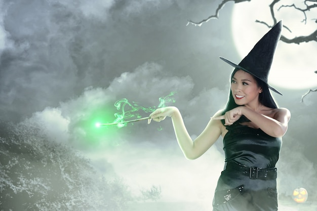 Asian witch woman using the wand with magic shine